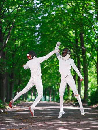 women fighting: Two rapier fencer women fighting over park alley, attacking each other in jumping Stock Photo