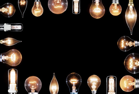 dimmer: Collage of many Edison lamps glowing over black background, copyspace frame Stock Photo