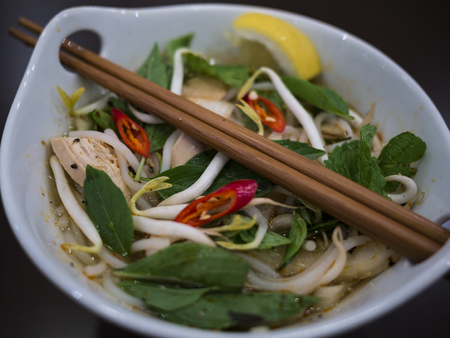 Beautiful and appetizing photo of a traditional vietnamese chicken noodle soup, also know as Pho Ga. In a white bowl with wooden background and luxurious wooden chopsticks. Amazing green mint and basil, and red chillies. Stock Photo