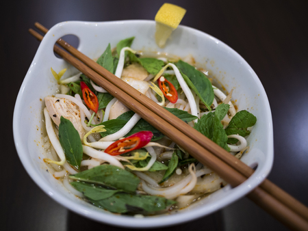 Beautiful and appetizing photo of a traditional vietnamese chicken noodle soup, also know as Pho Ga. In a white bowl with wooden background and luxurious wooden chopsticks. Amazing green mint and basil, and red chillies. 版權商用圖片