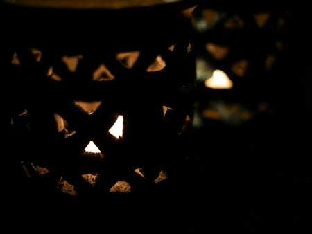Amazing close up of lit candles in a beautiful blue candle holder, with a black background.