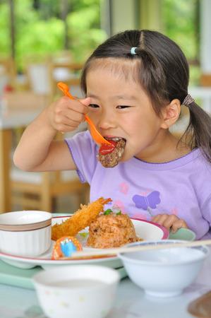 niños comiendo: La muchacha come menú de la cena para los niños Foto de archivo