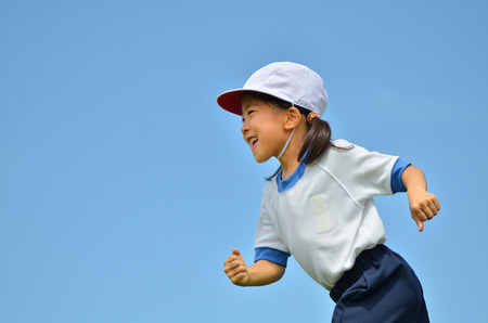 Girl in blue sky gym clothes, red white hat Stock Photo
