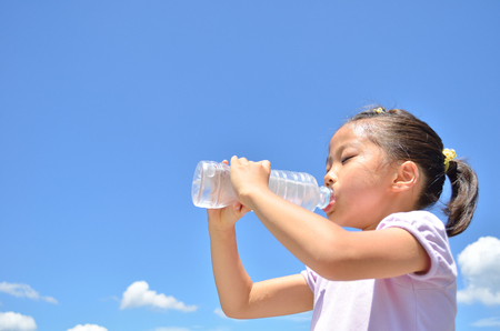 Girl drinking water blue sky 스톡 콘텐츠