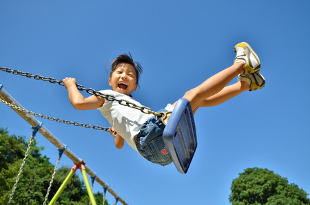 A girl playing on the swings in the Park 스톡 콘텐츠