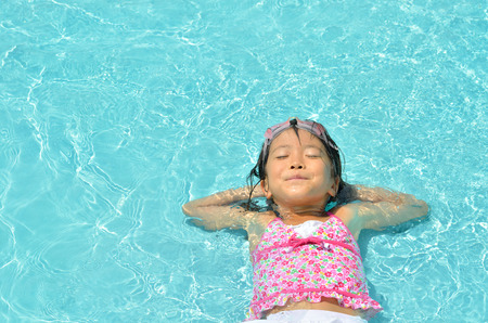 Girl resting in a pool 스톡 콘텐츠