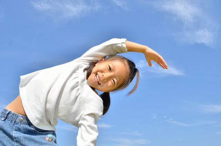 elementary age girl: Girls gymnastics in the blue sky Stock Photo