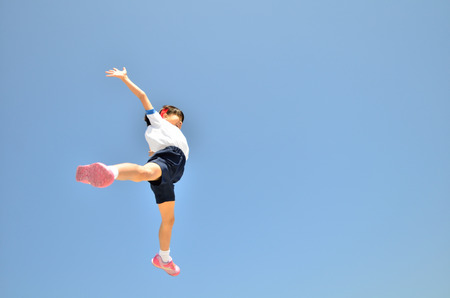 sprawled: Girls jumping in the sky gym clothes Stock Photo