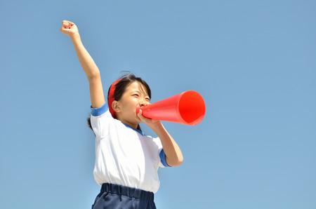 Meisjes bij de blauwe lucht sportschool uniform, met een megafoon Stockfoto