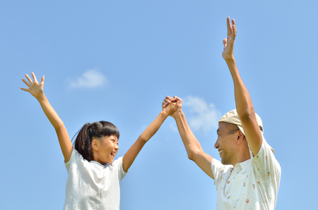 raise: Parent-child raise their hands in the sky