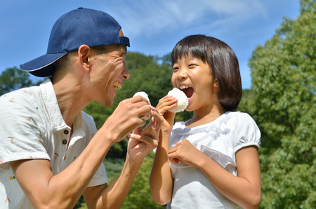 japanese people: Parents and children eat rice ball