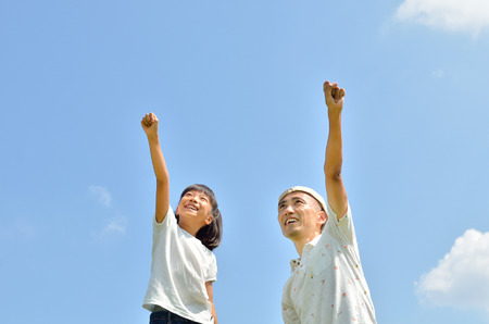 Parent-child raise their hands in the sky
