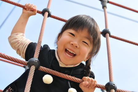 mignonne petite fille: Une fille jouant à l'aire de jeux dans le parc