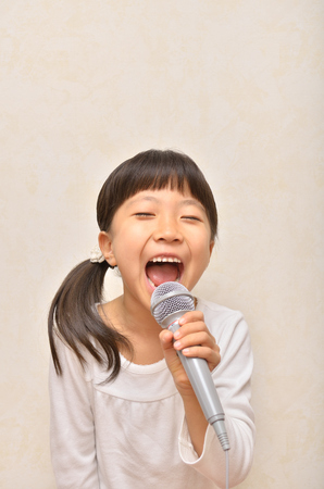Girl singing in a microphone 스톡 콘텐츠