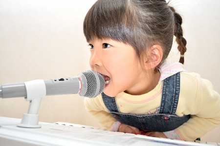 upper school: Girl singing in a microphone Stock Photo