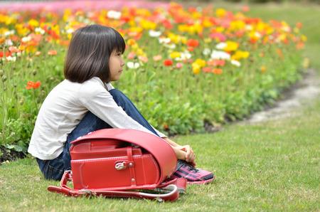 花の庭で座っている女の子