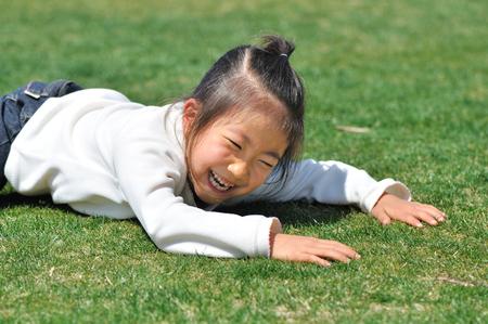 lie down: Girls lie down in the grass