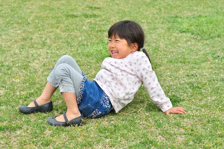 sit: Girls sit on the lawn