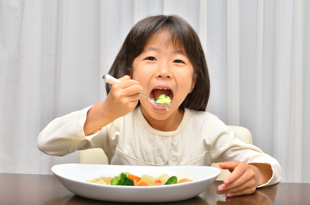 Girl eating delicious stew Stock Photo