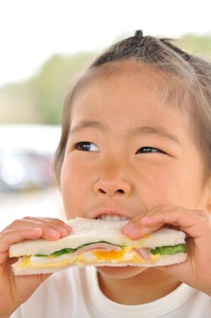 女の子は、おいしいサンドイッチを食べる。
