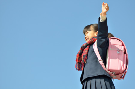 Girls of elementary school students raise their hands in the sky