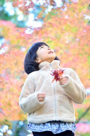 upper school: Girls enjoying the autumn leaves Stock Photo
