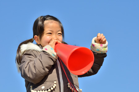 winter weather: Girls cheer in the blue sky (megaphone) Stock Photo