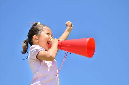 alegría niñas en el cielo azul (megáfono) Foto de archivo