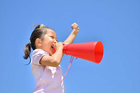 Girls cheer in the blue sky (megaphone) Standard-Bild