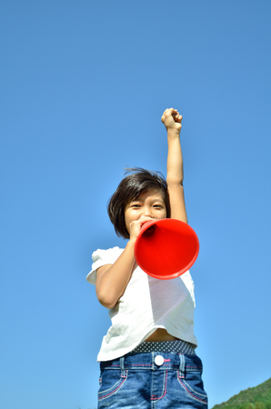 laughing out loud: Girls cheer in the blue sky (megaphone) Stock Photo