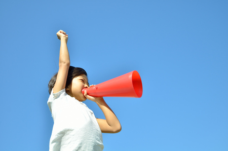 Girls cheer in the blue sky (megaphone) Stock Photo