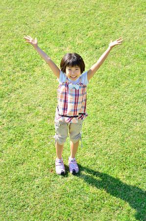 raises: Girl raises hands in the grassland