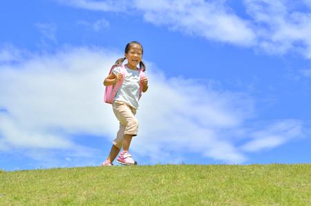 Elementary school children walking in the grassland