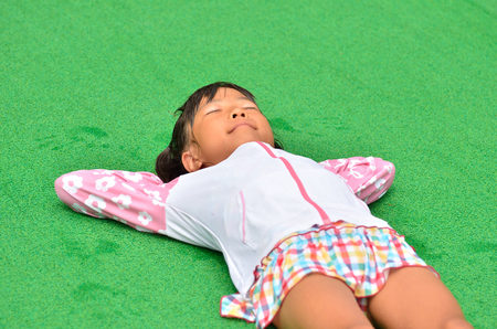 Girl lie down at the poolside Stock Photo