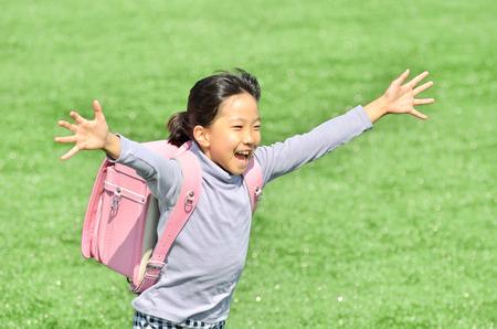 Elementary school children running in the grassland