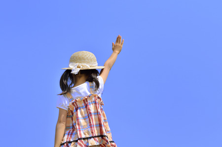 raise hand: Girl raise hand in the blue sky (straw hat, back) Stock Photo