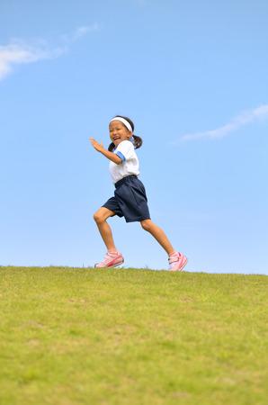 Girl running in the blue sky Stock Photo