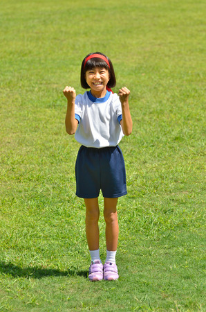 sports day: Girl cheering in the grassland (Sports day) Stock Photo