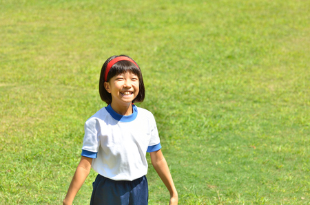 sports day: Girl smile in the grassland (Sports day) Stock Photo