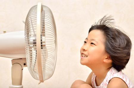 女の子が電動ファンで冷却