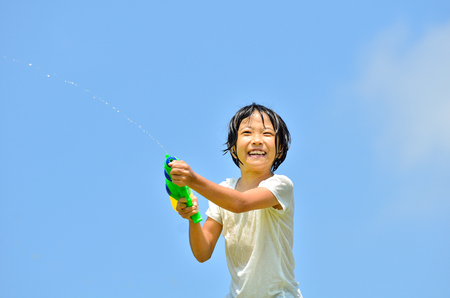 Girl playing with water pistols