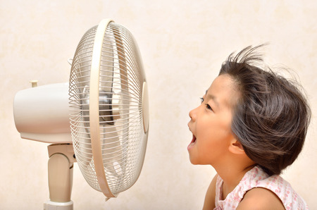 Girls cooled down by the electric fan Stock Photo