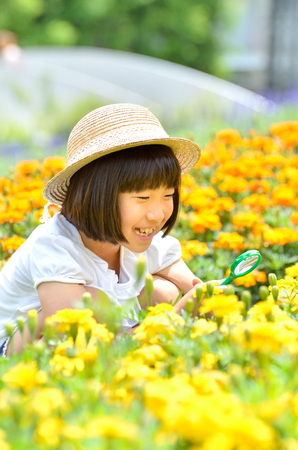 Girl watching the flowers with a magnifying glass