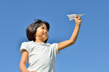 vigor: Girls fly paper plane in the blue sky Stock Photo
