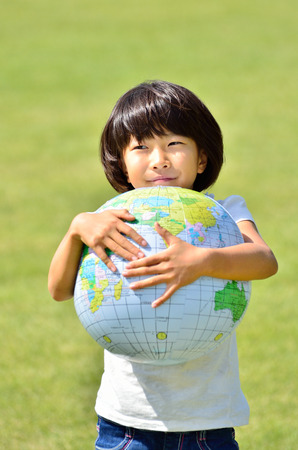 Girls hold earth in the grassland Stock Photo