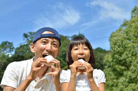Japanese parent and child eat rice ball Stock Photo