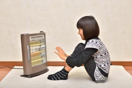 暖かいストーブの上の女の子 写真素材