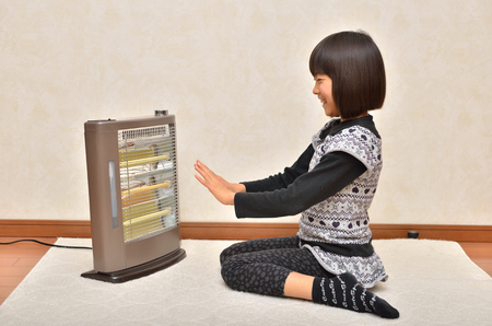 Girl warm on the stove 스톡 콘텐츠