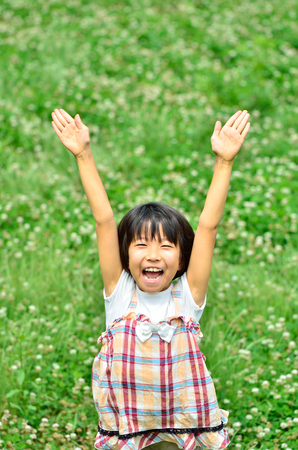 Girls raise hands in the grassland Stock Photo
