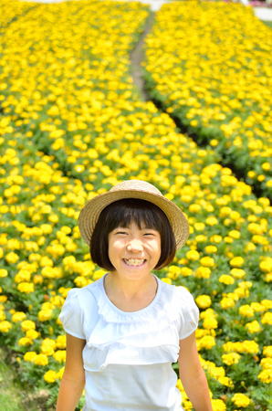 Girls smiling in the flower garden (straw hat